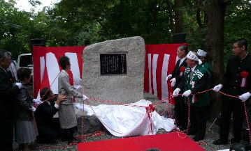 歌碑の除幕式、左側は佐伯総長(左端)、および横山・赤木両家の家族ら、右側は現恵迪寮執行委員長と中瀬名誉会長・横山会長ら同窓会役員